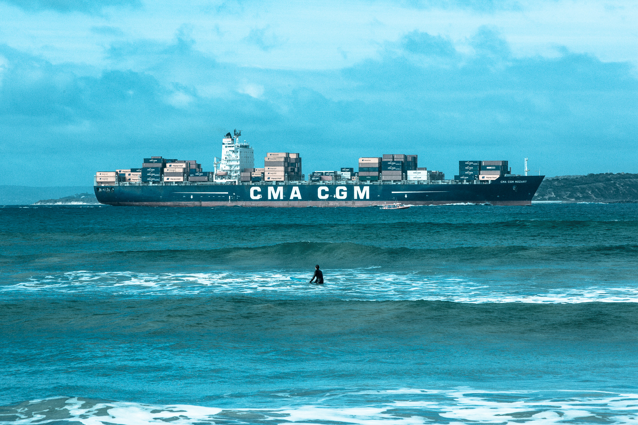A surfer waits for a wave while watching a CMA CGM container ship sail through Point Lonsdale on 2nd July 2016. Large ships have to follow a precise S-shaped course with a qualified pilot onboard to help them pass between the narrow 2km wide heads.